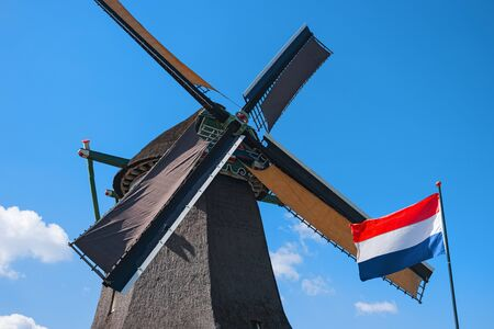 Old windmill and waving flag, Zaanse Schans, Netherlands. Typical dutch mill. Rural landscape. Symbol of the Netherlands Stock Photo
