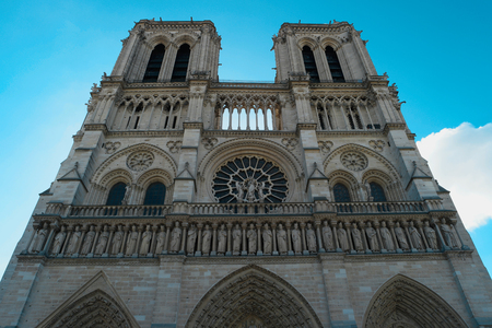 Notre Dame de Paris Cathedral. French gothic style. Front view on blue sky background. Close up. Beautiful european architecture, Paris, France, Europe