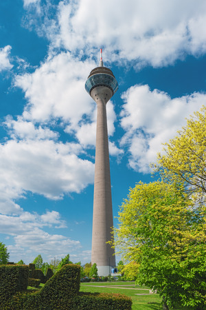 TV tower Rheinturm, Dusseldorf, Germany, Europe. Famous Rhine Tower is a 240.5 metre high telecommunications tower, tallest building in Dusseldorf. View from park. Modern european architecture