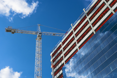 Tower crane and modern building under construction. Industrial construction crane. New residential development. Construction site on blue sky background Stock Photo