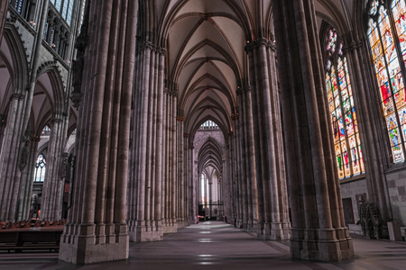 Cologne gothic cathedral interior, Germany, Europe. Famous monument and most visited place, symbol of Cologne. Inside Cologne Dom, nave, columns, stained glass and ceiling.
