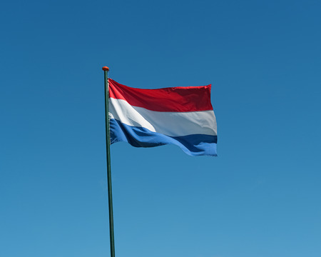 Flag of the Netherlands on flagpole waving in the wind. Netherlands national official flag on blue sky background. Patriotic symbol, banner