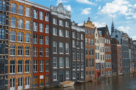 Traditional dutch old houses in center of Amsterdam, Netherlands, Europe. Typical historic buildings on canal in Amsterdam. Colorful facades of dutch dancing houses. Beautiful summer cityscape