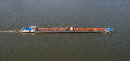 Waste disposal on large heavy cargo ship. Boat with scrap metal. Environment concept, vessel shipping garbage in sea. Aerial view of boat carrying waste on river. Barge transports construction debris