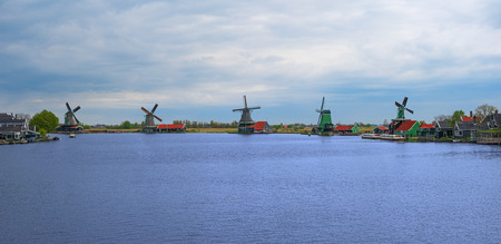 Panorama of Zaanse Schans windmills and water channel, North Holland, Netherlands, Europe. Panoramic view of dutch mills in famous authentic village, Zaan river. Row of old dutch traditional windmills Editorial