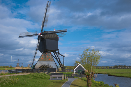 Traditional dutch windmills and water canal, Kinderdijk, Netherlands, Benelux, Europe. Typical old dutch mill, scenery. Beautiful rural landscape. Famous village Kinderdijk. UNESCO world heritage site