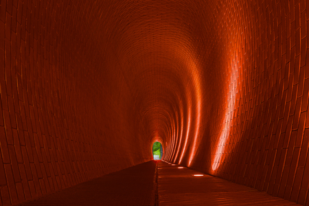 Empty long arched brick pedestrian tunnel, Prague. Orange brick walls, strip of lighting lamp. Bright arch. Underground mysterious footpath for walkers. Underpass and nature at end of tunnel, concept
