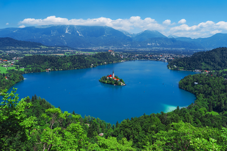 Aerial view of Lake Bled, Alps, Slovenia, Europe. Mountain alpine lake. Island with church in Lake Bled. Summer landscape. Castle and mountains in background. Famous travel destination of Slovenia