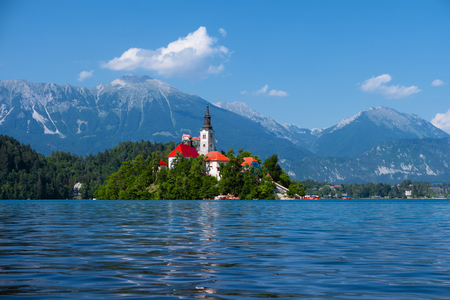 Lake Bled, Alps, Slovenia, Europe. Summer scenery. Mountain alpine lake. Island with church in Lake Bled. Beautiful landscape. Castle and mountains in background. Famous travel destination of Slovenia