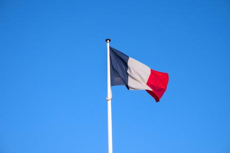 French national official flag on blue sky background. Symbol of France. Patriotic french banner, design. Flag of France on flagpole waving in the wind Reklamní fotografie