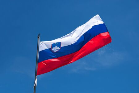 Flag of Slovenia on flagpole waving in the wind. Slovenian national official flag on blue sky background. Patriotic symbol, banner