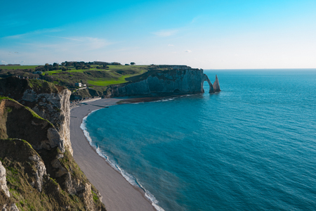 Beach, ocean and cliffs, Etretat, Normandy, France, Europe. Natural arches, white chalk cliffs over Atlantic Ocean. Sea bay, landscape Popular landmark famous destination. Aerial view of Etretat beach