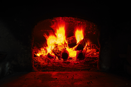 Firewood burning in brick oven, fire flame closeup. Flame on burning wood in stone fireplace from firebricks Reklamní fotografie