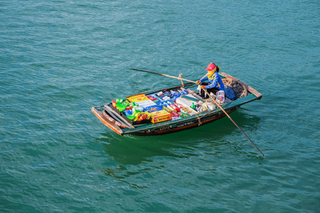 Halong, Vietnam, May 15, 2017: Floating market, Ha Long Bay, Vietnam. Woman sells drinks and snacks from boat, Halong Bay. Merchant selling goods. Asian floating market. Food and fruit seller in boat