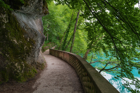 Hiking trail in forest, Lake Bled, Alps, Slovenia. Pathway lane way, green trees. Beautiful road, alley in park. Path in summer forest. Empty walkway. Scenic nature. Natural scenery. Summer landscape 스톡 콘텐츠