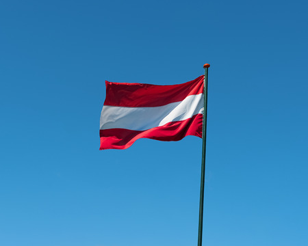 Flag of Austria on flagpole waving in the wind. Austrian national official flag on blue sky background. Patriotic symbol, banner