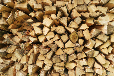 Pile of chopped firewood logs. Stack of wood pieces. Pine timber. Woodpile. Rural home concept. Storage of firewood Dry chopped logs Heat generation Wood processing Stock for winter Texture background