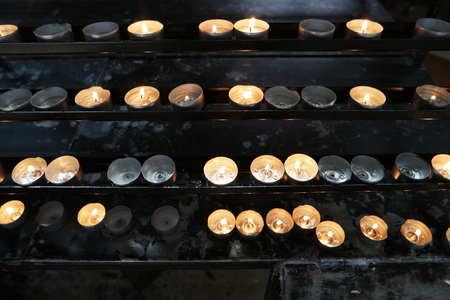 Burning candles in church. Concept of religion. Sacred light, dark background. Bright yellow light in the evening, close-up. Many lighted candles in candlesticks on black
