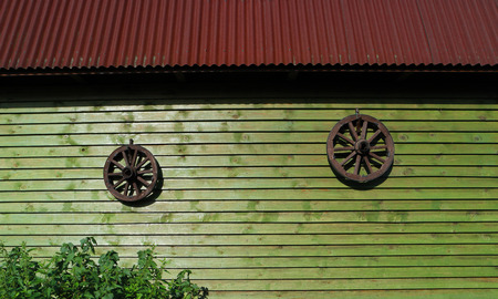 Two ancient wooden rustic wagon wheels from carriage hangs on wall of wooden house. Two vintage circle from cart on wall of old log house. Old retro hand spinning wheel. Rural log hut, russian village