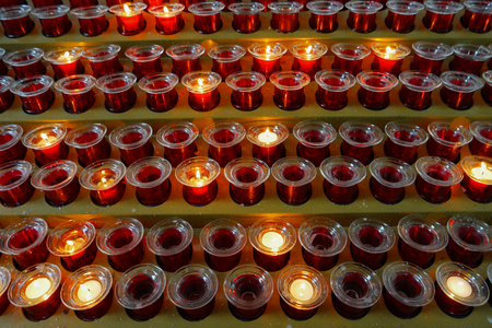 Many lighted candles in candlesticks. Sacred light. Burning candles in church. Concept of religion. Bright yellow light in the evening, close-up 스톡 콘텐츠