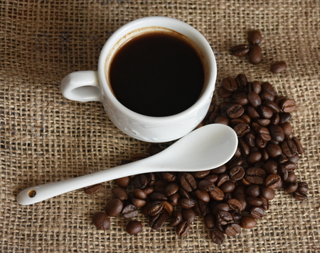 Coffee cup, teaspoon and coffee beans on jute canvas Stock Photo