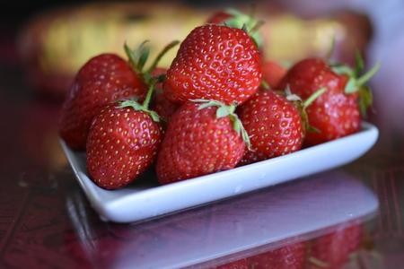 Fresh strawberries in white bowl Stock Photo