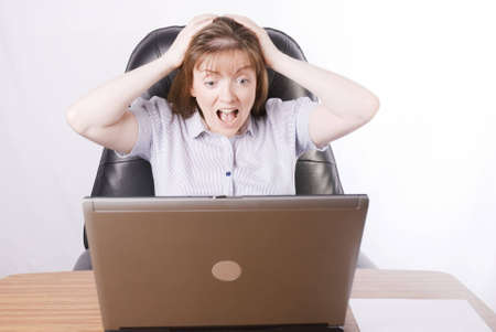 aghast: a horizontal image of an office secretary looking on in horror as her laptop crashes