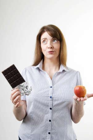 1 つの手にチョコレートとりんごを食べて、彼女に最適なものを決定する試みのバーでかなり若い女性の垂直方向の画像 写真素材
