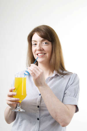 sipping: a vertical image of a pretty young woman with a glass of orange juice in hand sipping from a blue straw