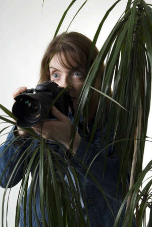 a vertical image of a young female paparazzi taking a picture from behind a bush