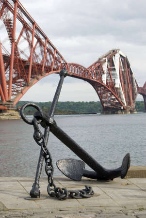 a vertical image of a ships anchor on the quayside with the Forth Rail Bridge in the background photo