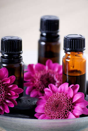 essential: a vertical image of three essential oils and flowers in a dish