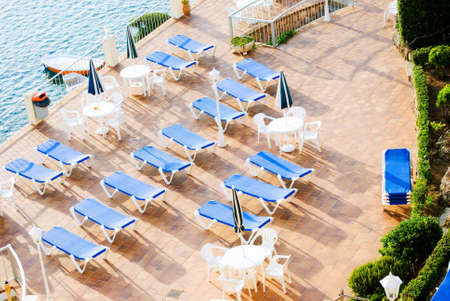 loungers: a horizontal image of rows of blue sun loungers on a patio in early morning sunshine viewed from a high vantage point Stock Photo