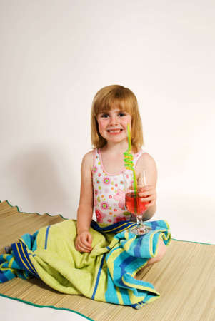 beach mat: a vertical image of a lovely little girl pretending to be on a beach sitting on a mat in her bathing costume with a glass of fruit juice in her hand, isolated against a plain background Stock Photo