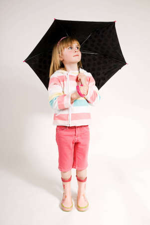rainwear: a vertical image of a young girl standing with her umbrella up and looking up at the clouds,isolated against a plain background