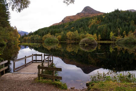 pap: A horizontal image of  a mountain in Glencoe Scotland called the Pap reflecting in the Loch with the surrounding forest and a boat jetty in the foreground Stock Photo