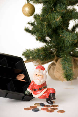 a vertical image of a sad poor santa sitting on the edge of a coinbox with a few pennies and two buttons suggesting poverty at christmas photo