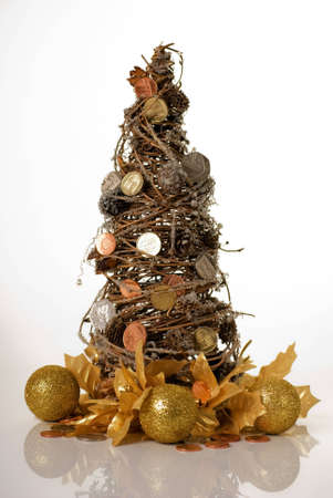 willow tree: a vertical image of a willow christmas tree decorated with coins to suggest money doesnt grow on trees at christmas