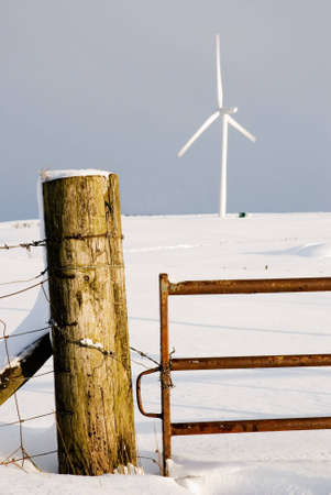 snowscene: a vertical image of a snowscene with fence post and turbine Stock Photo