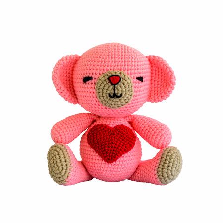 白で隔離される手作りかぎ針編みピンクのクマのぬいぐるみ