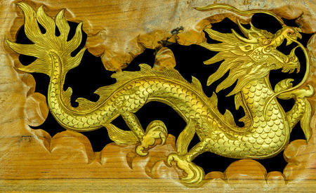 The wooden carved Chinese dragon on black background photo