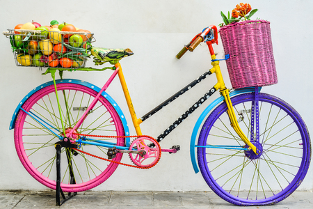 flower and fruit in the basket on a colorful bicycle photo