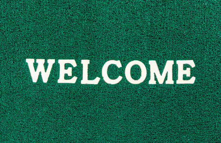 welcome mat: green doormat and welcome text for background