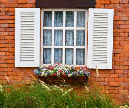 white window: open white window on red brick wall and flower in wooden vase Stock Photo