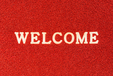 red doormat and welcome text for background photo