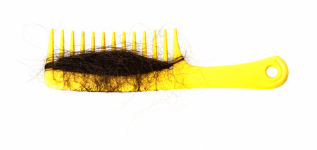 Hair loss problem and yellow comb isolated on white background photo
