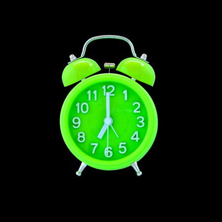 Groene wekker geïsoleerd op zwarte achtergrond
