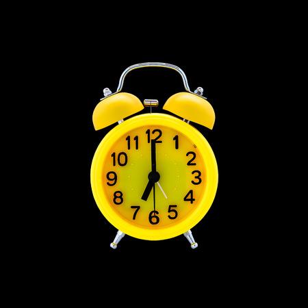 Gele wekker geïsoleerd op zwarte achtergrond