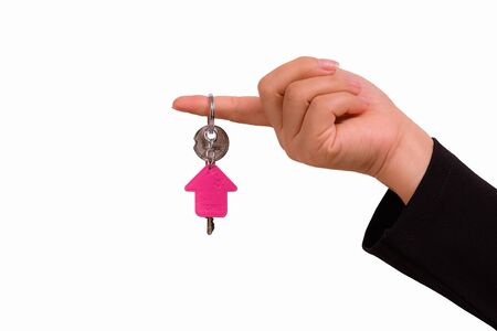 keychain: Hand of woman with a keychain in the shape of the house isolated on white background
