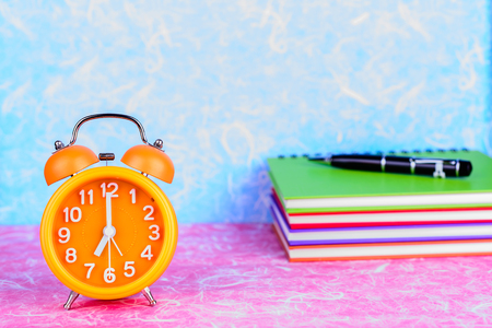 time clock: retro orange alarm clock on table with note book and pen on colorful wall background